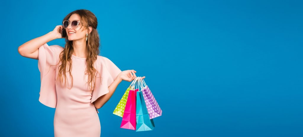 young stylish sexy woman in pink luxury dress, summer fashion trend, chic style, sunglasses, blue studio background, shopping, holding paper bags, talking on mobile phone, shopaholic